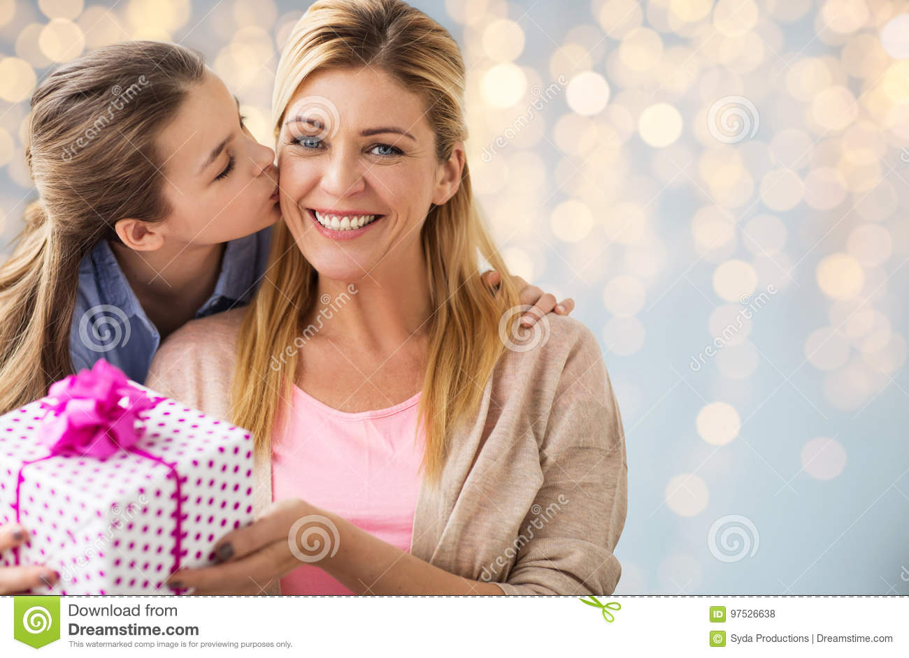 Girl giving birthday present to mother over lights