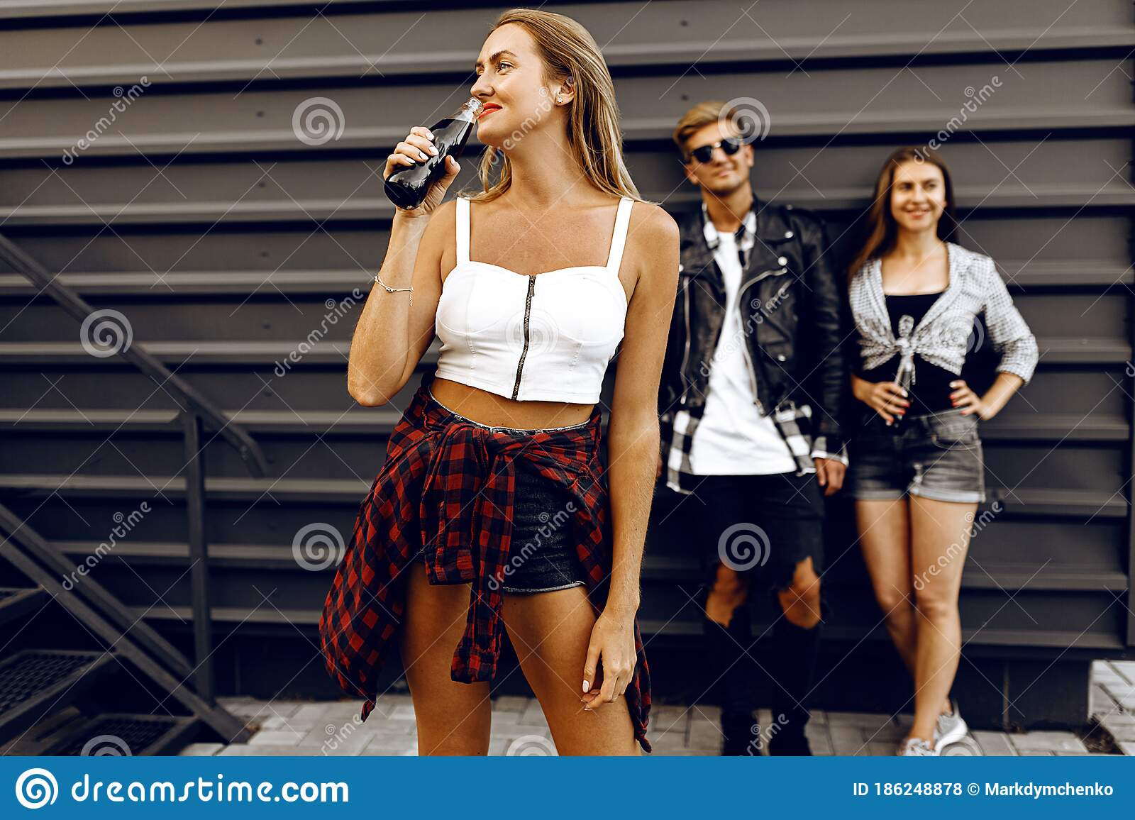 Girl With A Glass Bottle Of Drink Against The Backdrop Of Her Friends A Summer Party In The City Stock Photo Image Of Happiness Friendship 186248878