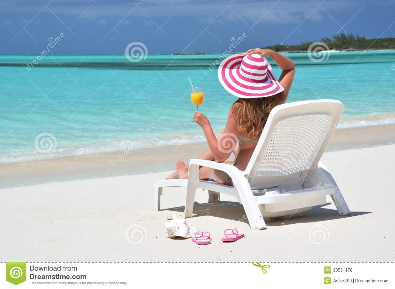 Girl with a glass of orange juice on the beach