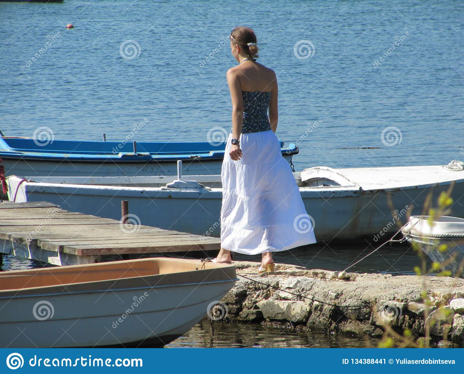 Girl goes along the beach on a Sunny day. ahead of the wooden bridge to which the boats are tied