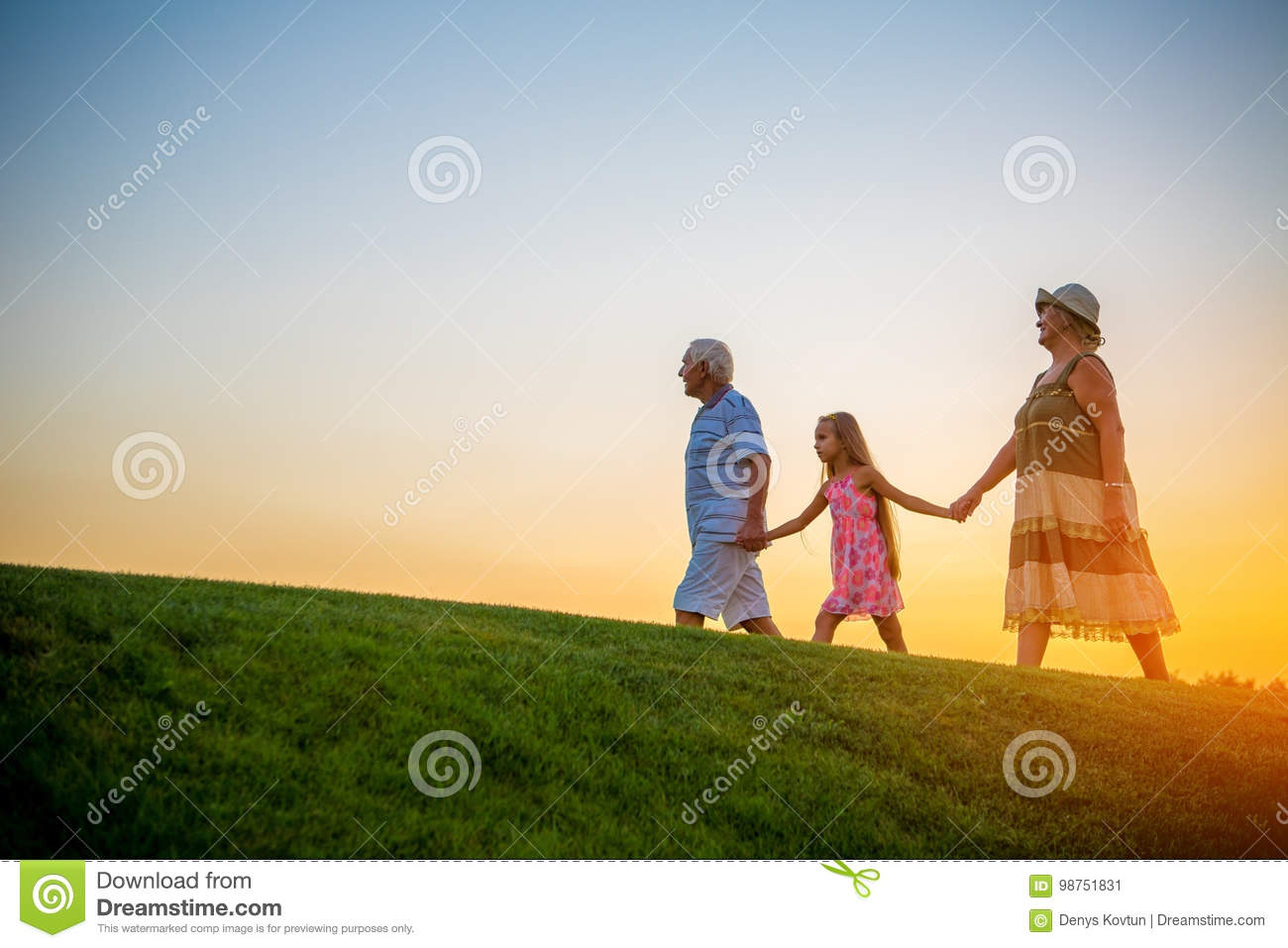 Girl with grandparents at sunset.