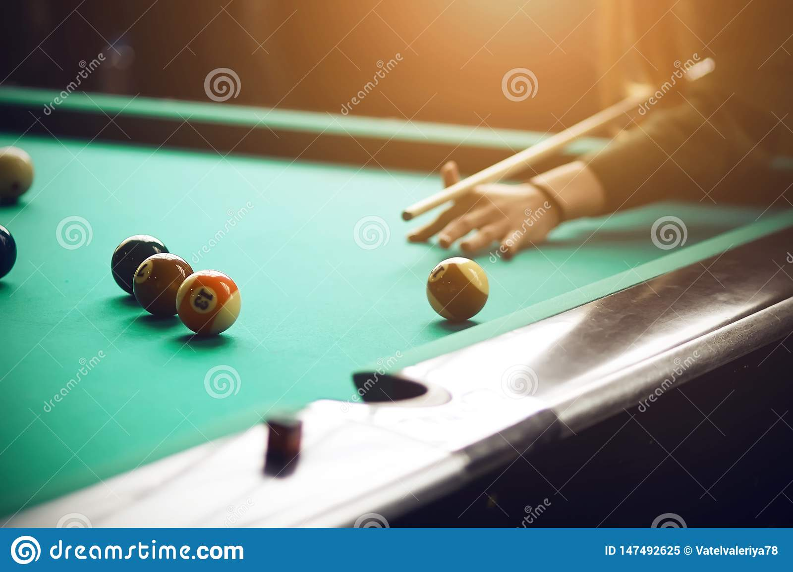 A girl in a green sweater playing Billiards