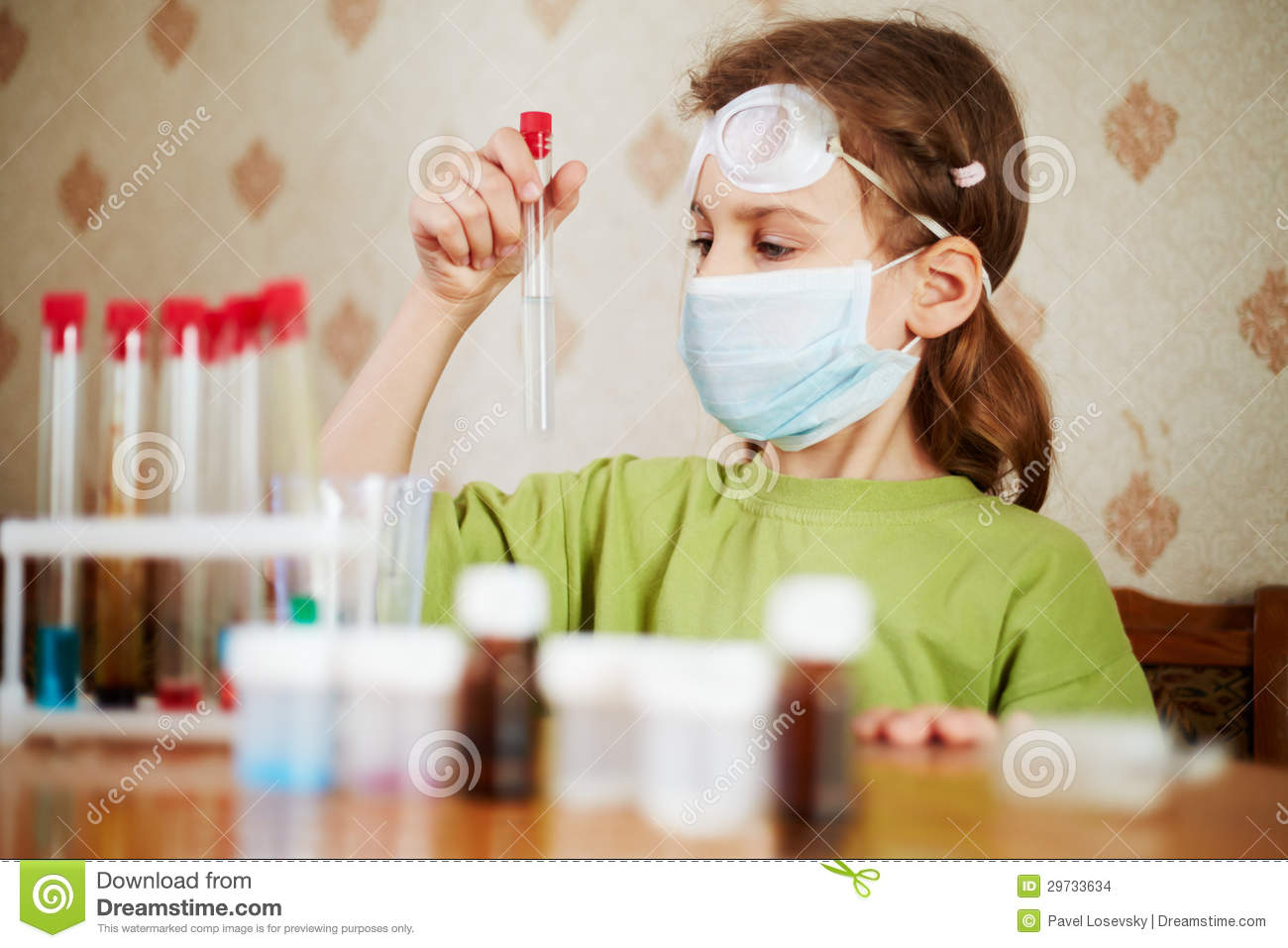 Girl in respirator attentively looks at test tube