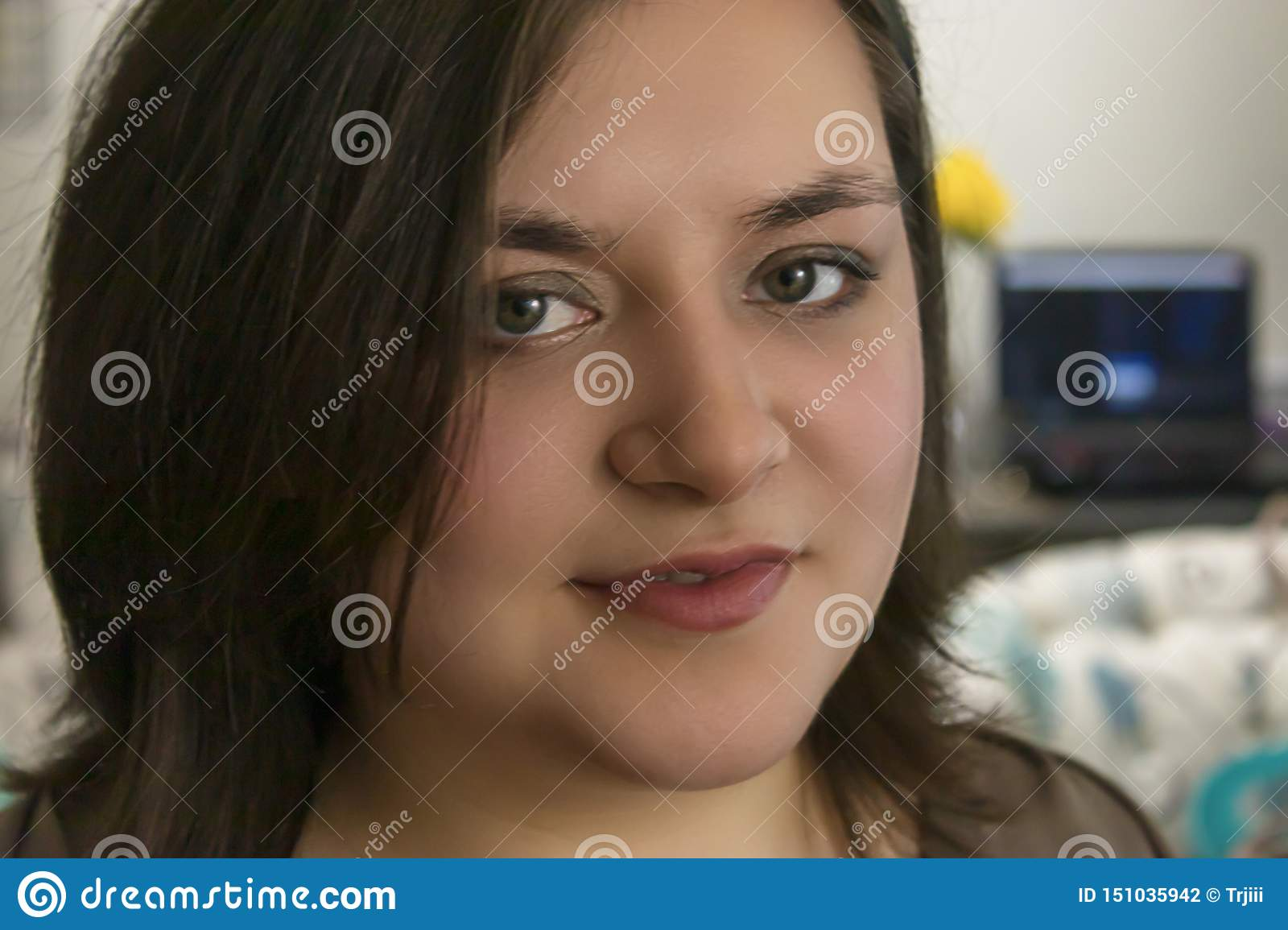 Girl grins softly in home in front of blurred computer