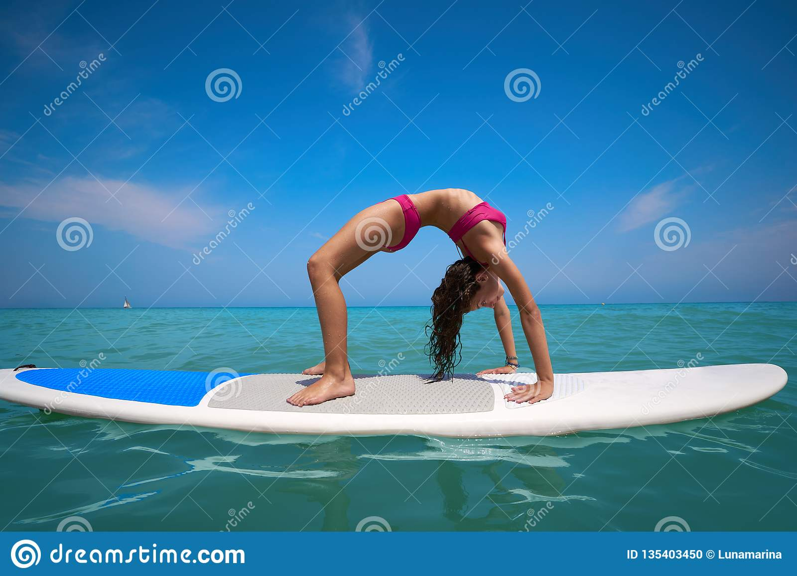 Girl gymnastics on paddle surf board SUP