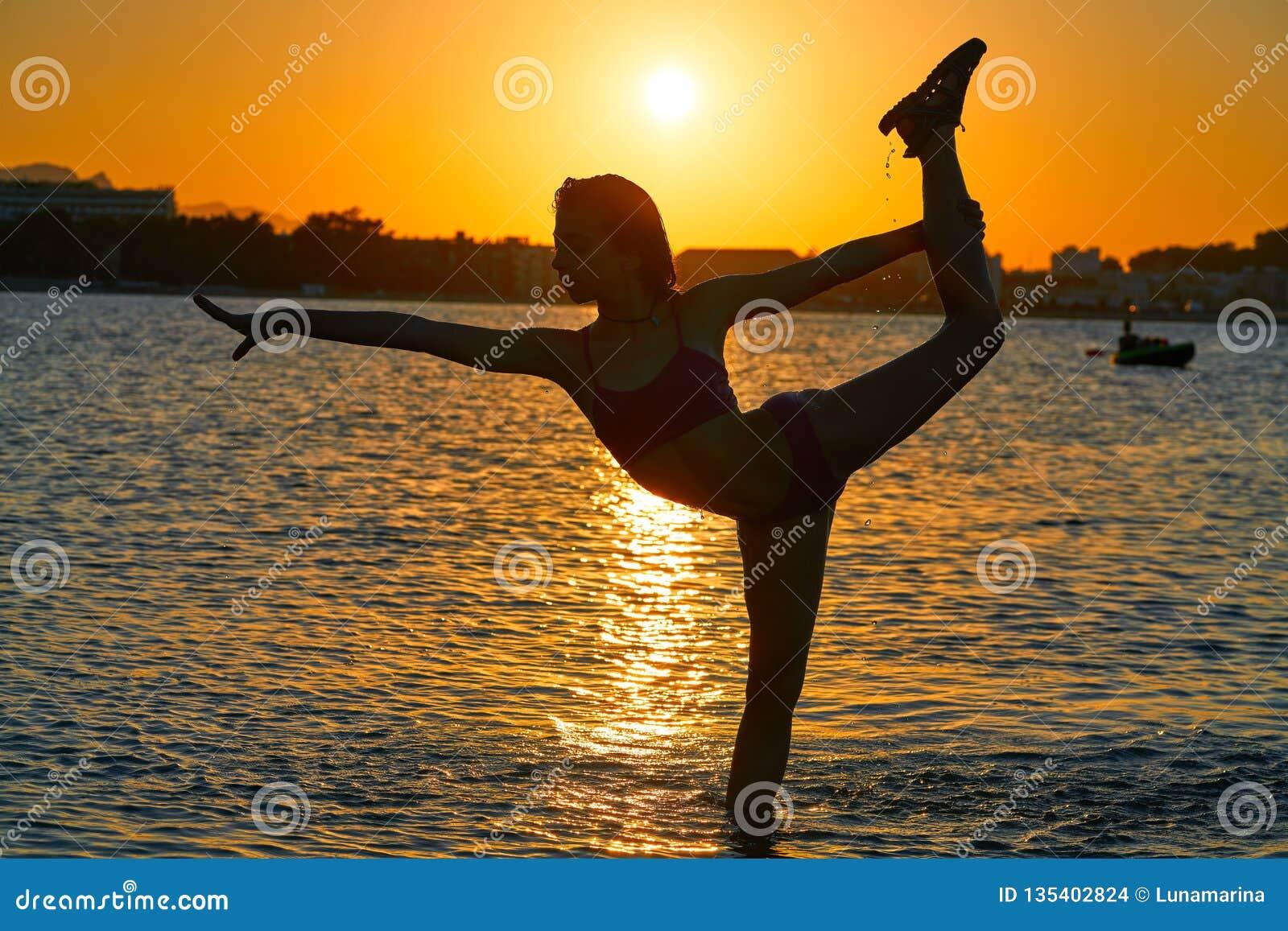 Girl gymnastics pose at sunset beach