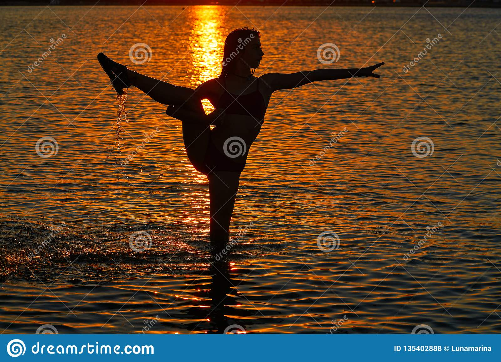 Girl gymnastics pose at sunset beach