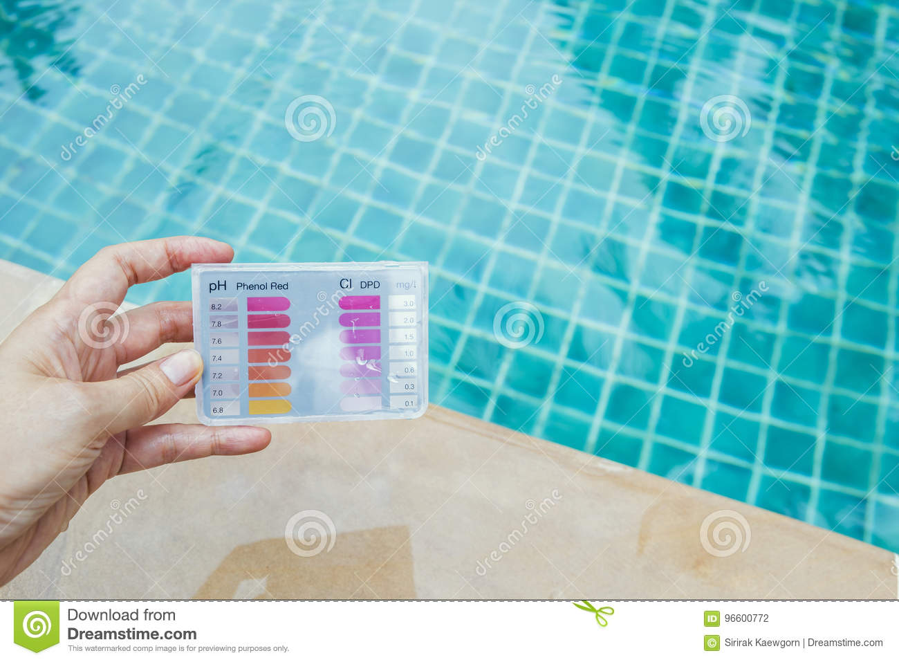 Girl hand holding water testing test kit over swimming pool