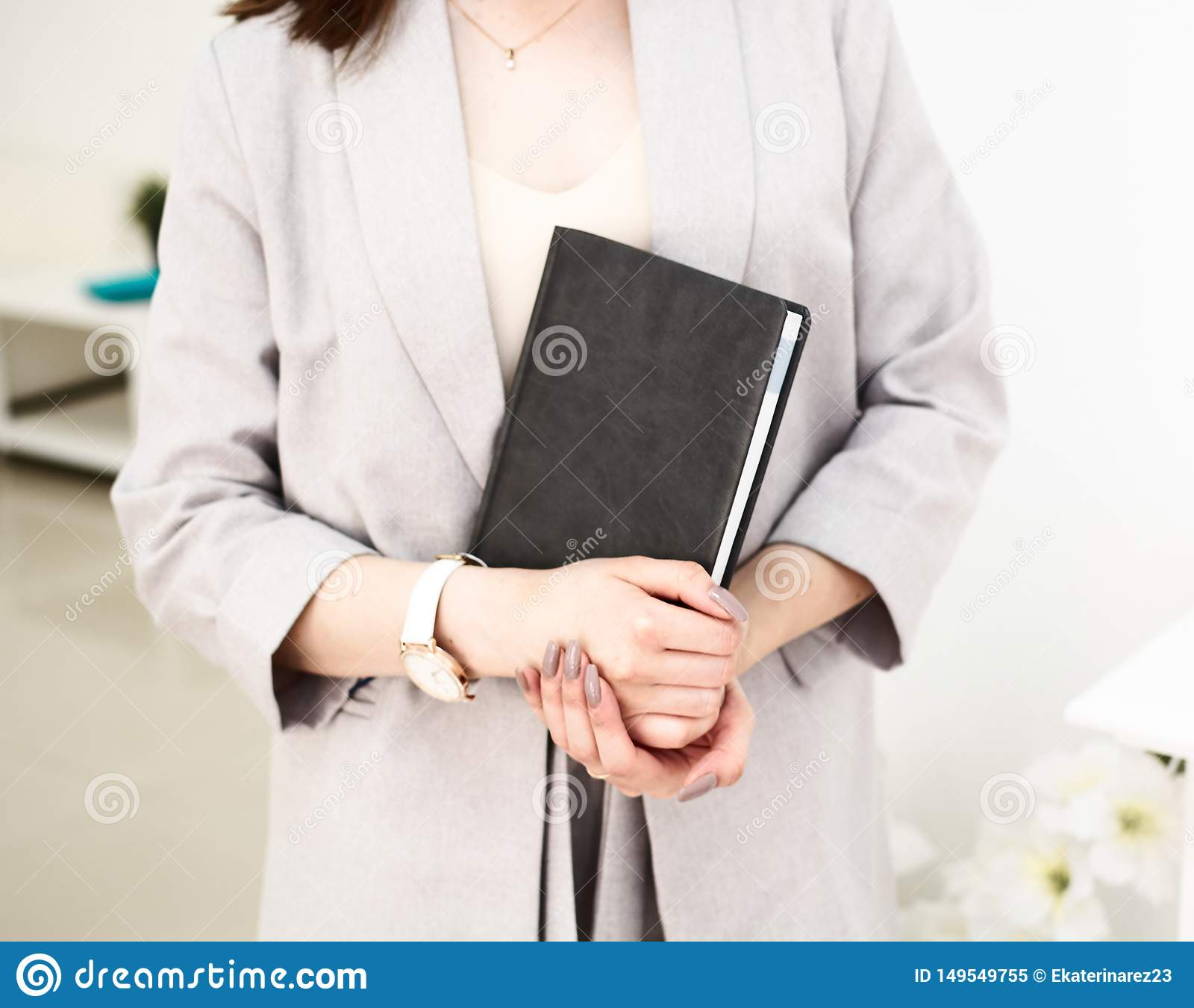 Girl is handing a book in her hands, dressed in grey jacket. She has a wrist watch on her hand. White background