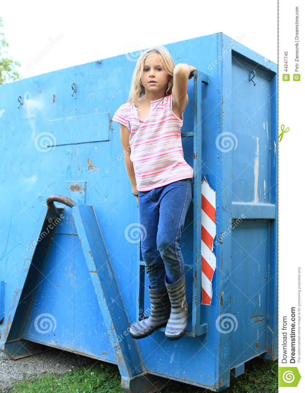 Little child - blond hairy girl in striped t-shirt, jeans and wellies ...