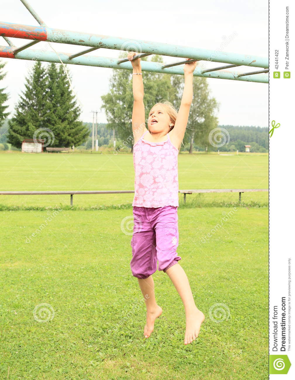 Girl hanging on obstacle course