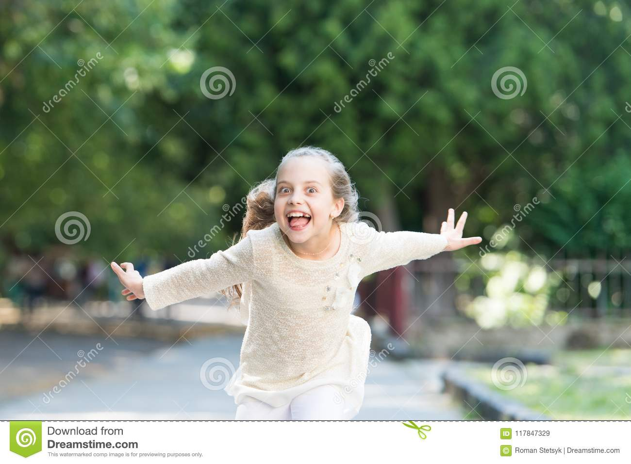 Girl on happy smiling face, nature on background. Child happy and cheerful enjoy walk in park. Happiness concept. Kid