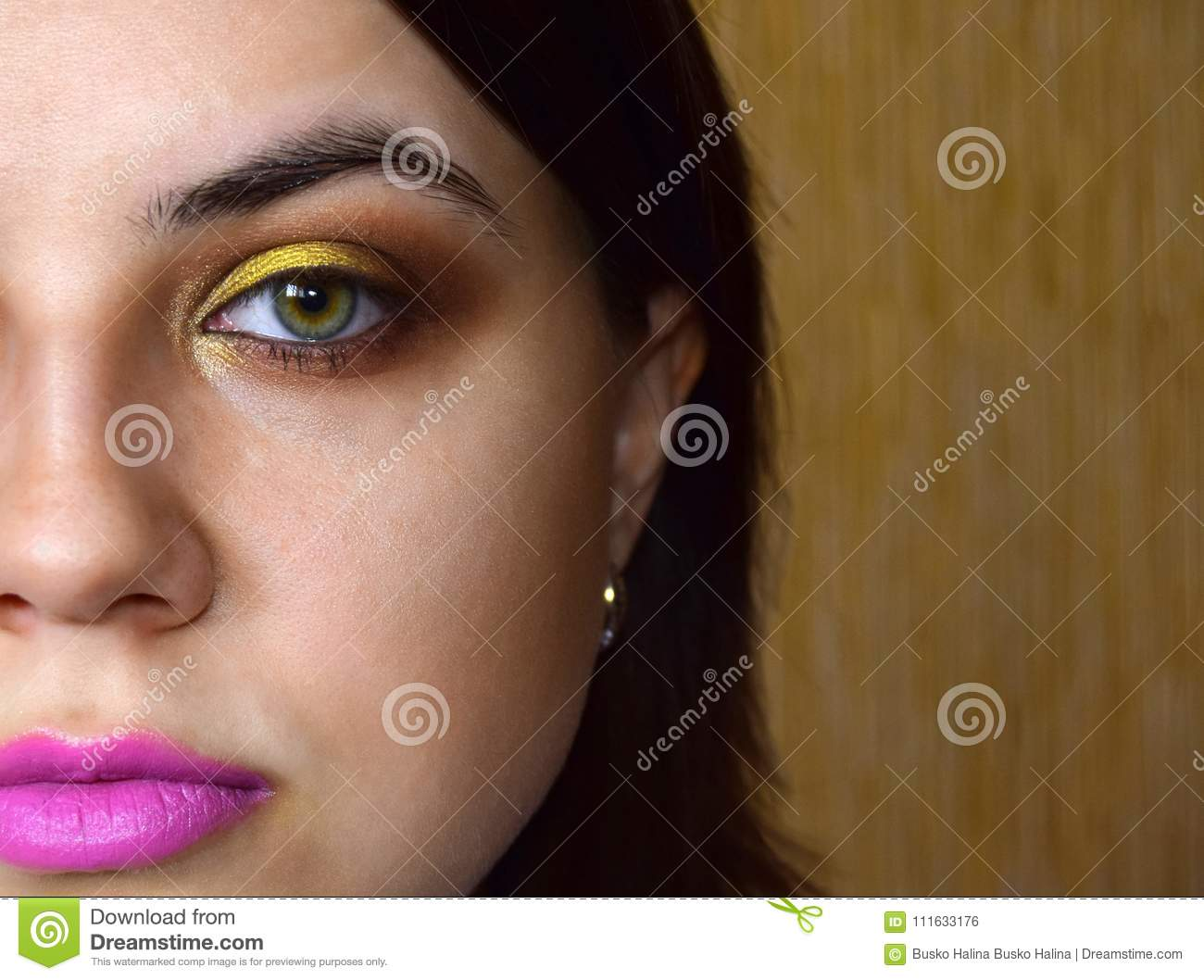The Girl Has A Makeup Of A Green Eye In Yellow And Gold Tones On