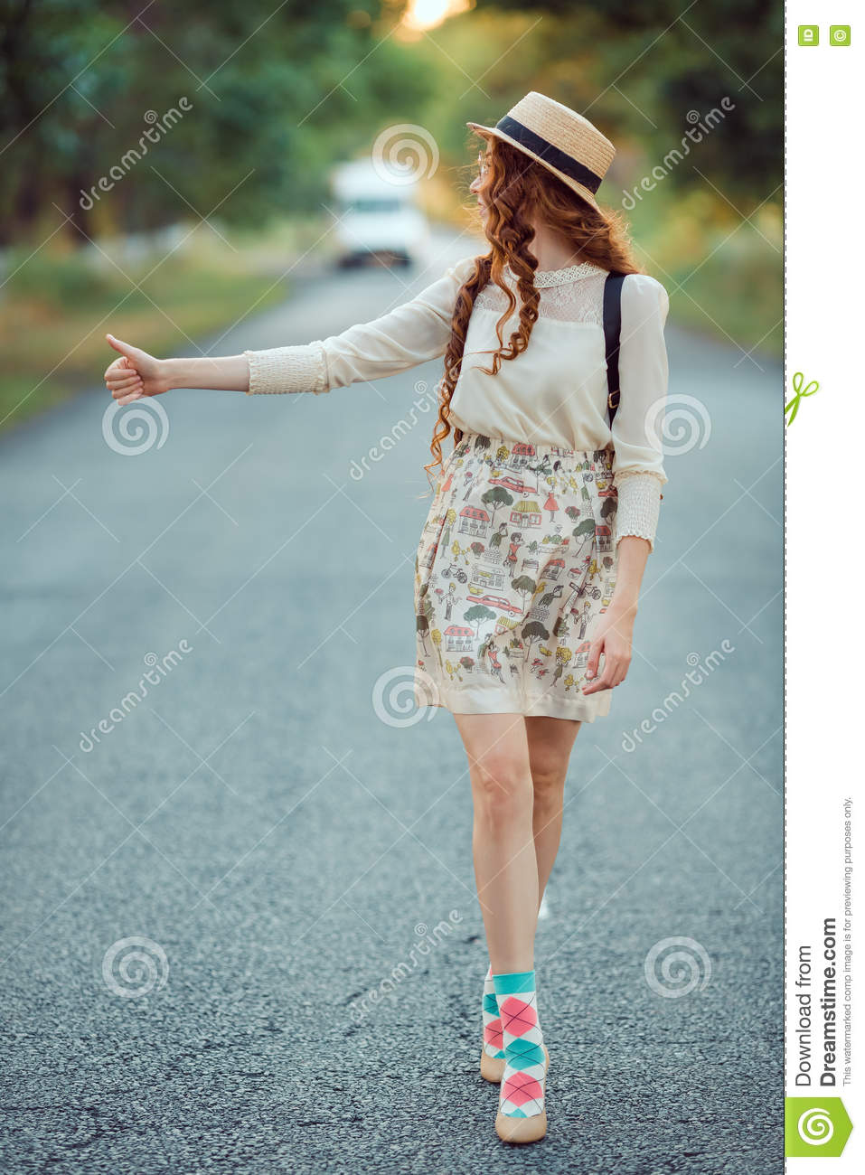Girl With Hat And Backpack Hitchhiking On The Road Stock