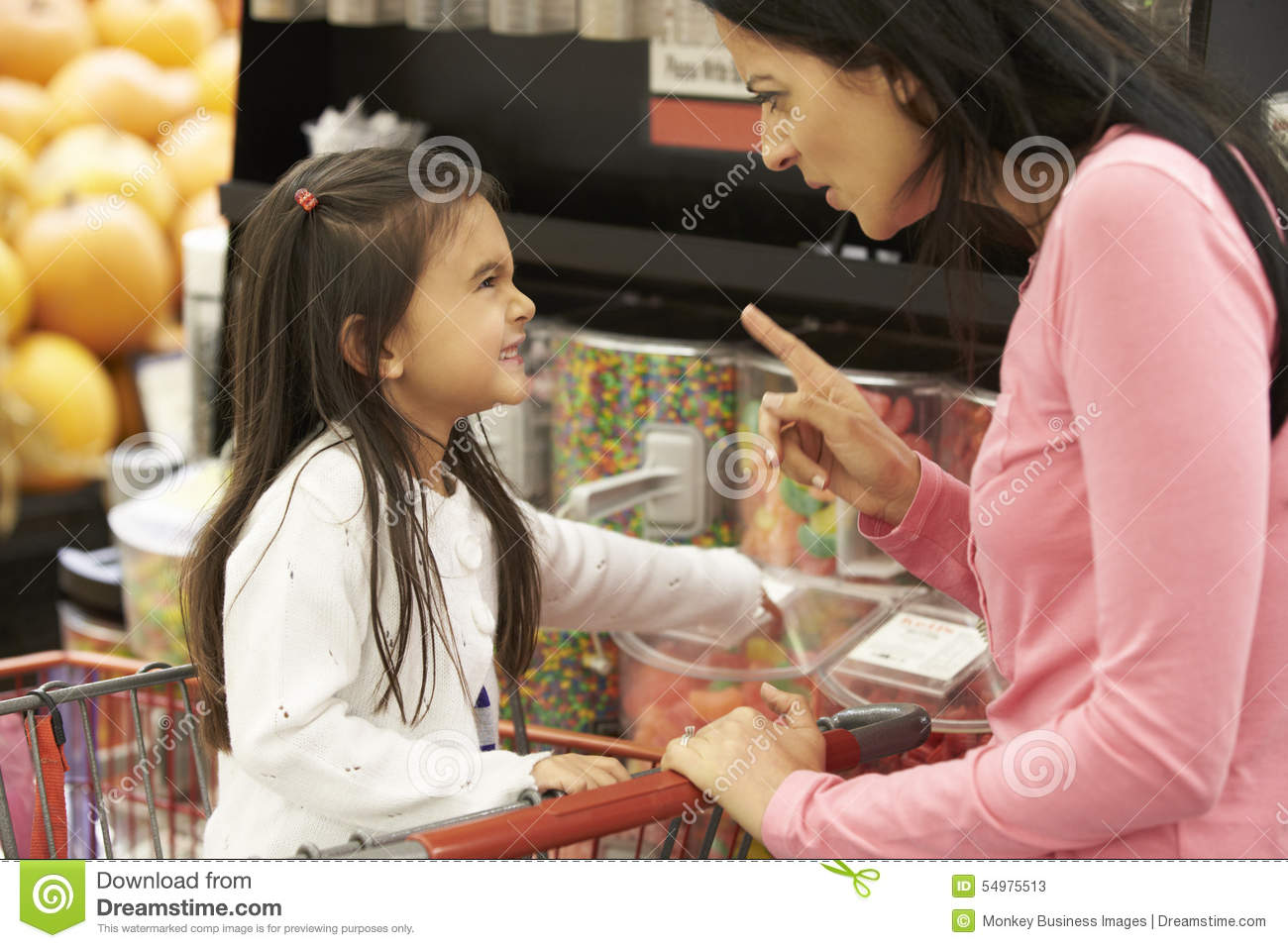 Girl Having Argument With Mother At Candy Counter In Supermarket