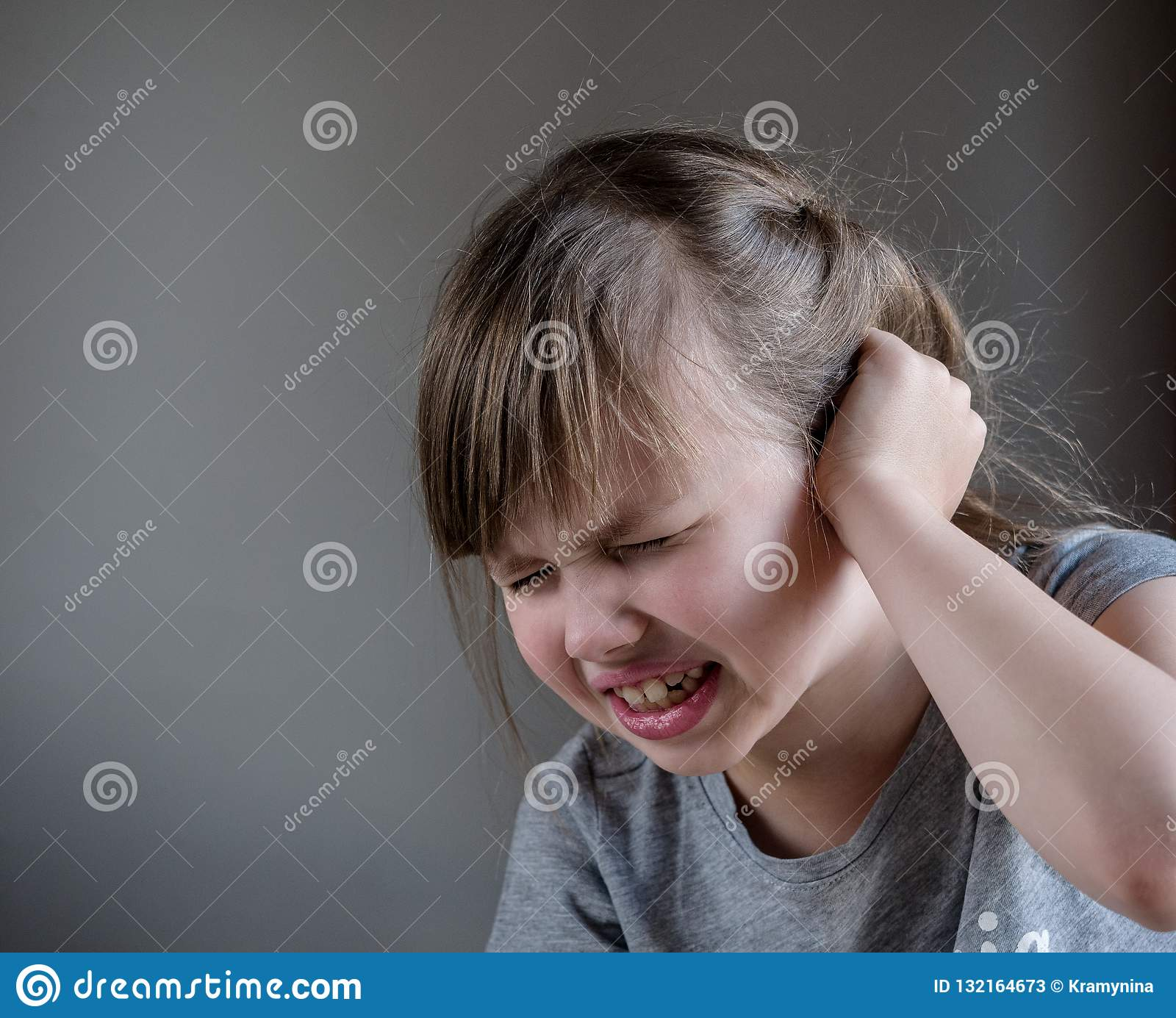 Girl having ear pain touching his painful head isolated on gray background