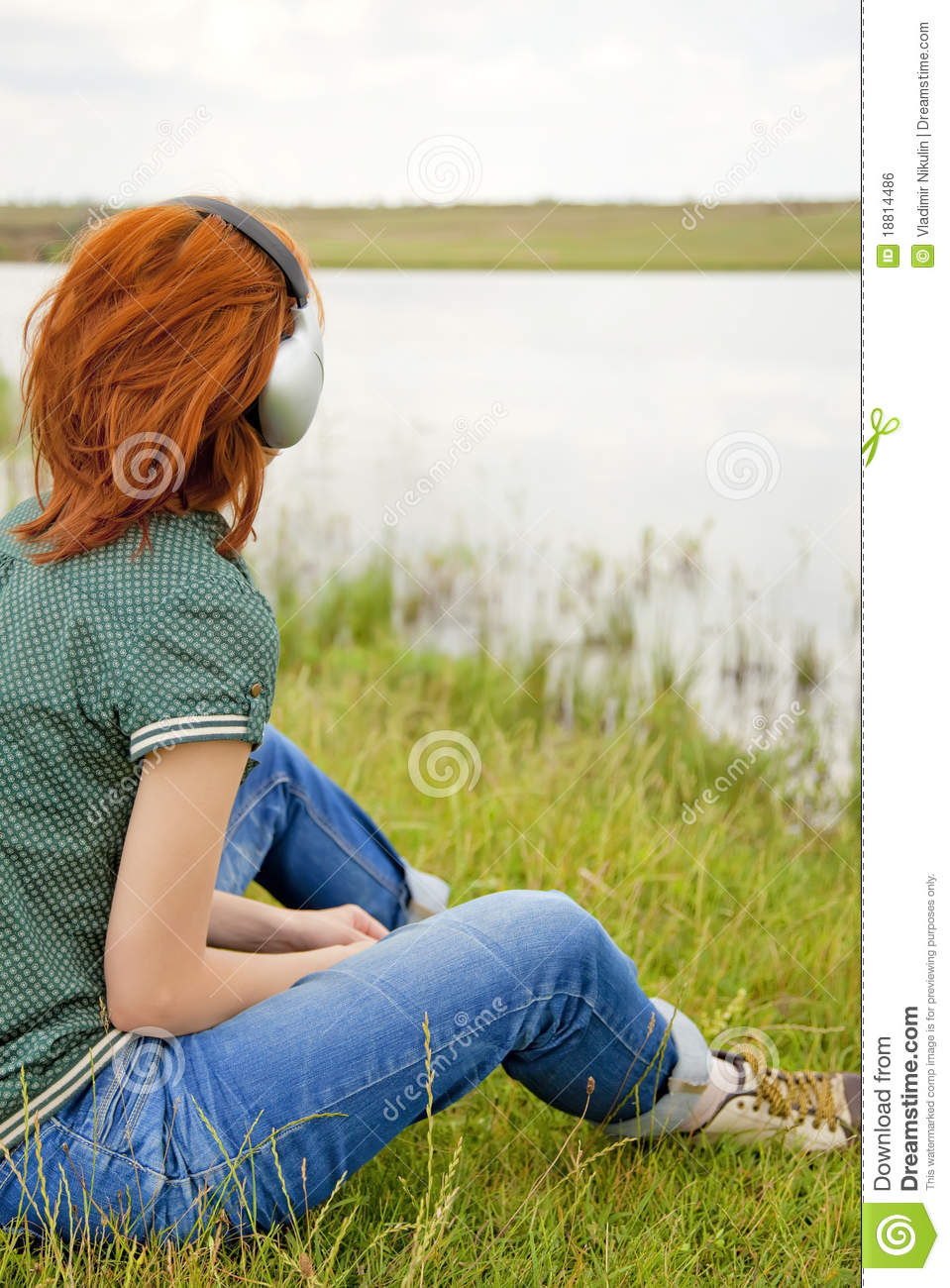 Girl with headphones at grass in spring time.