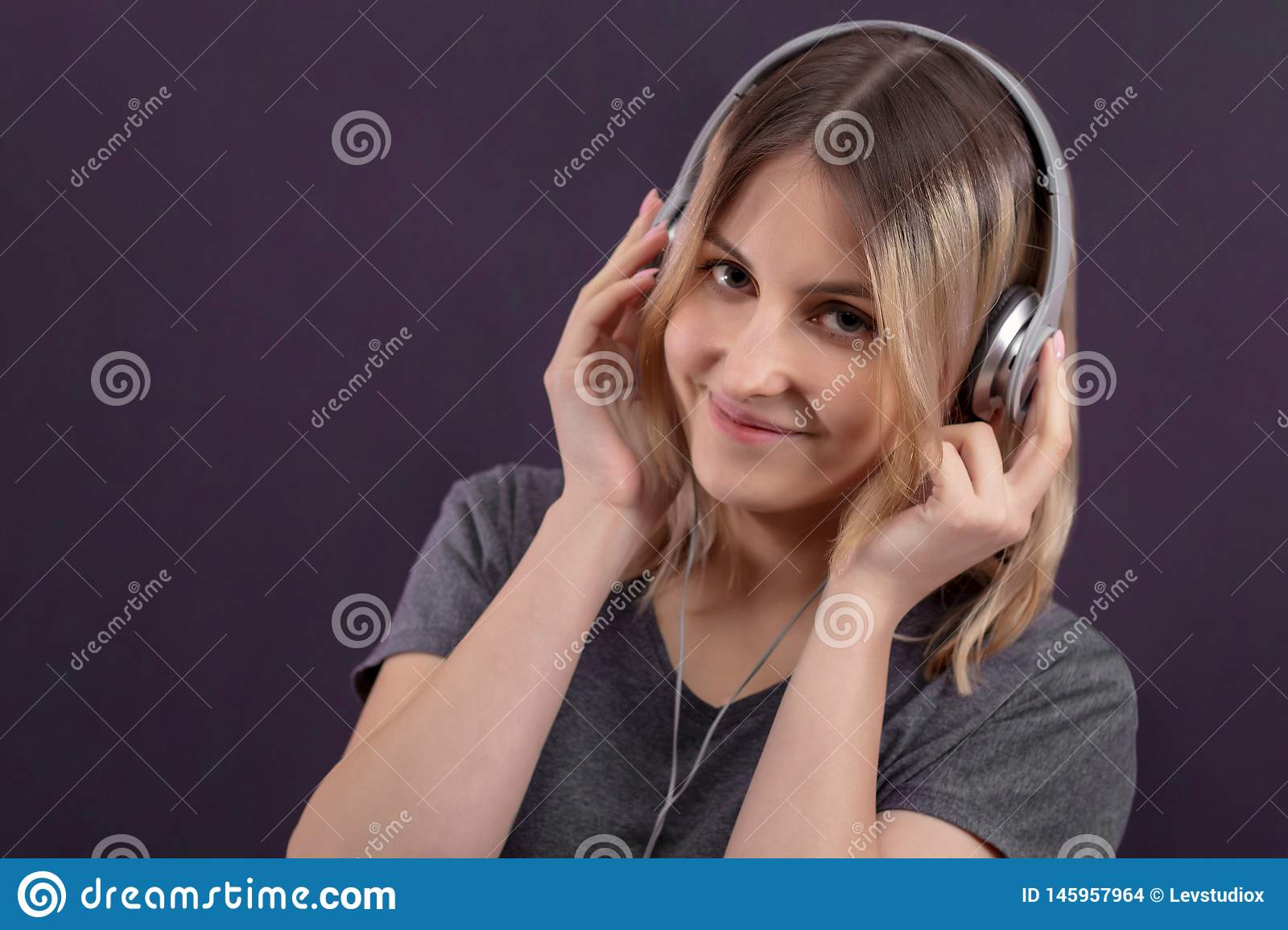 Girl in headphones smiling and listening to music, generation z