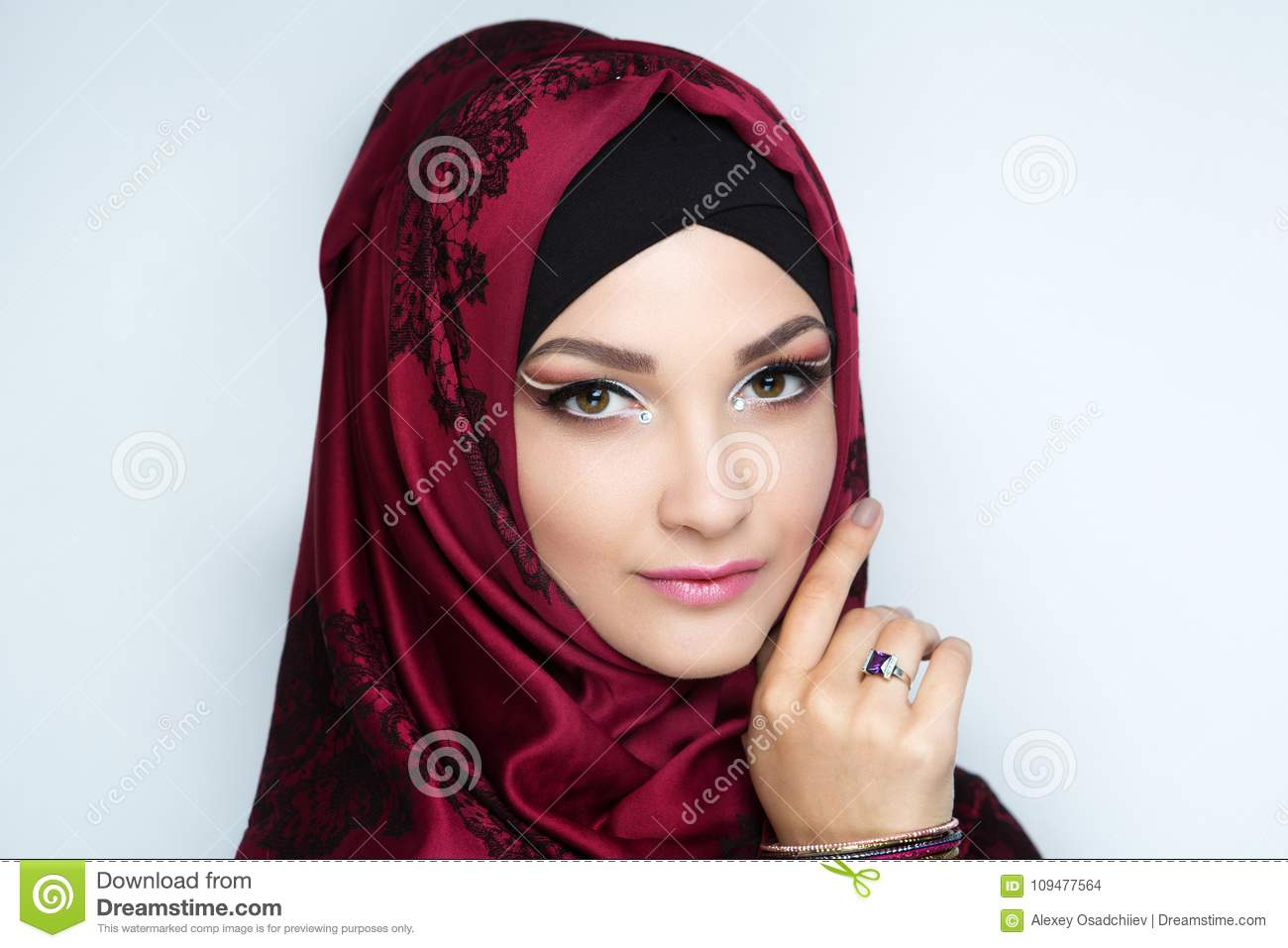 7270c569f2651 Young beautiful woman lady girl in a headscarf hijab. Professional  cosmetics bright makeup. Shiny lipstick lip-gloss, red shadows.
