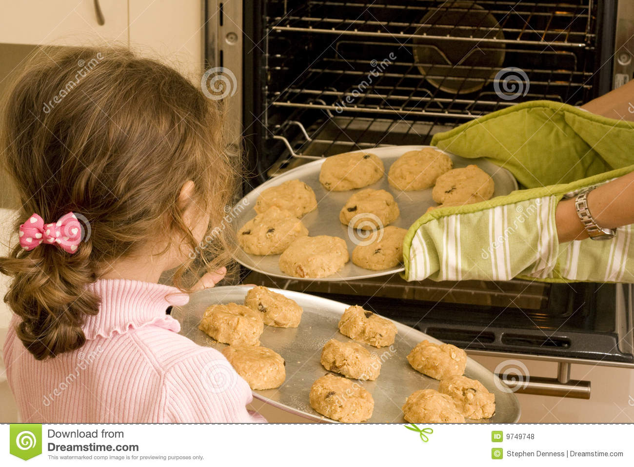 Girl Helping Mum Bake Cookies In Oven Royalty Free Stock