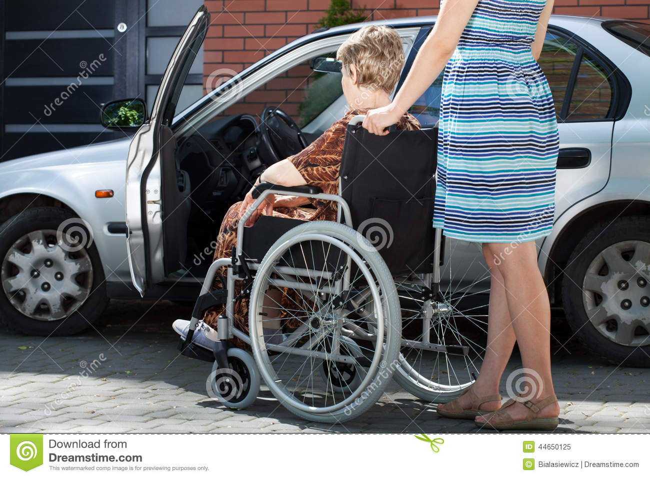 Girl Helping Woman On Wheelchair Getting Into A Car Stock