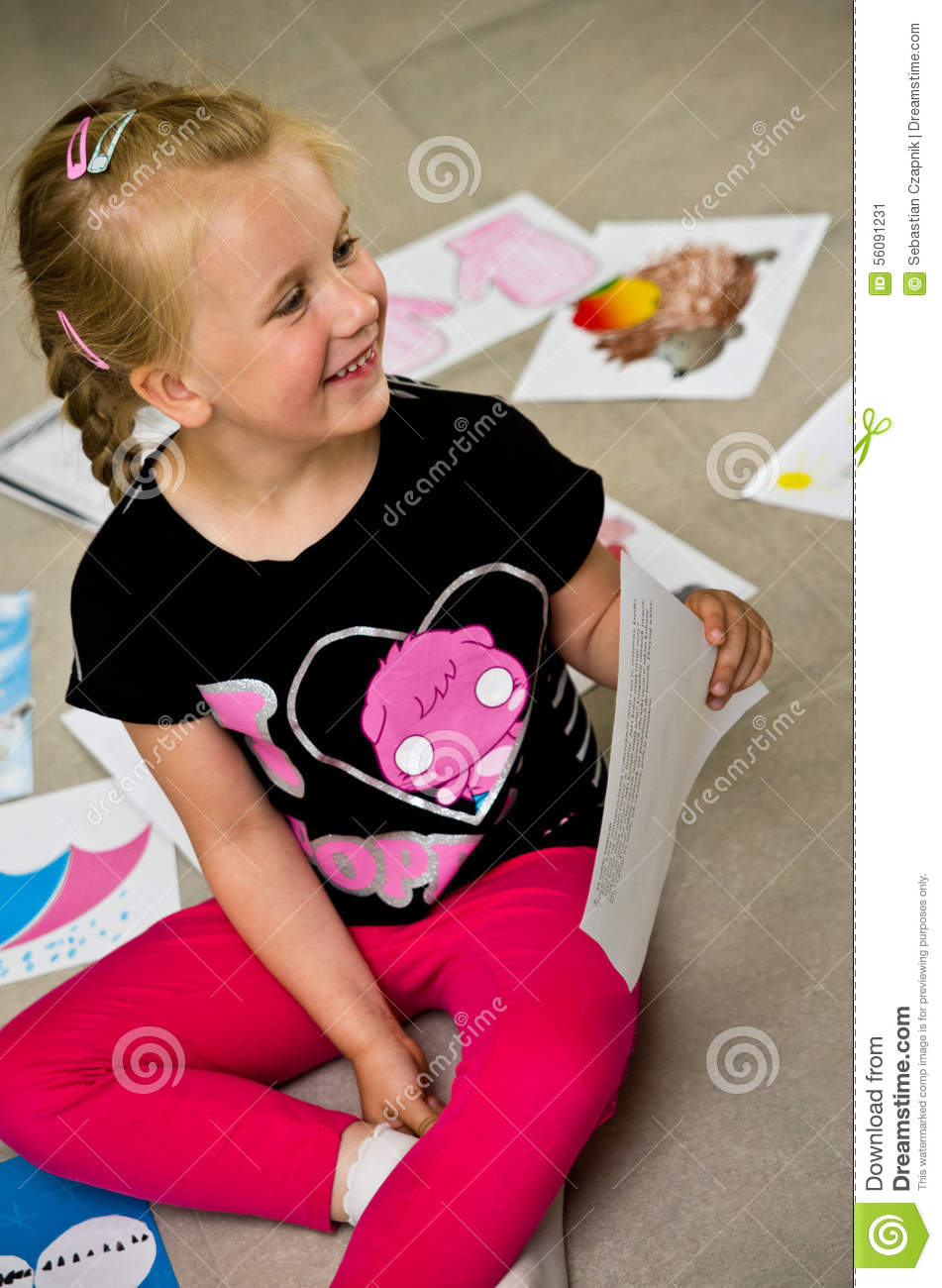Girl with her drawings on the floor