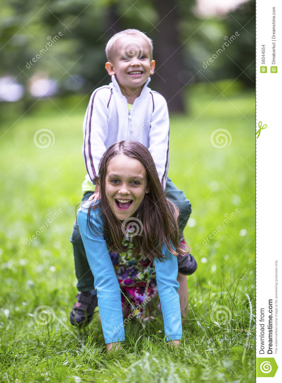 girl with her little brother playing in the green grass