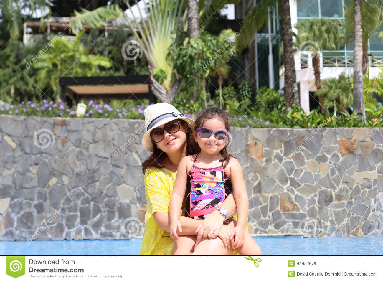 Girl with her mother outside swimming pool enjoying the summerwith their sunglasses