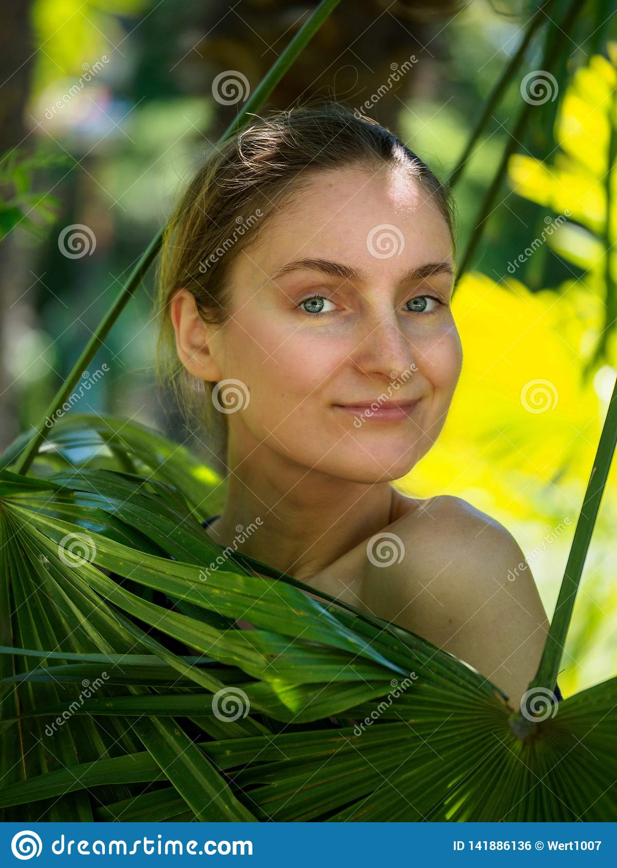 The girl hid behind the palm leaves