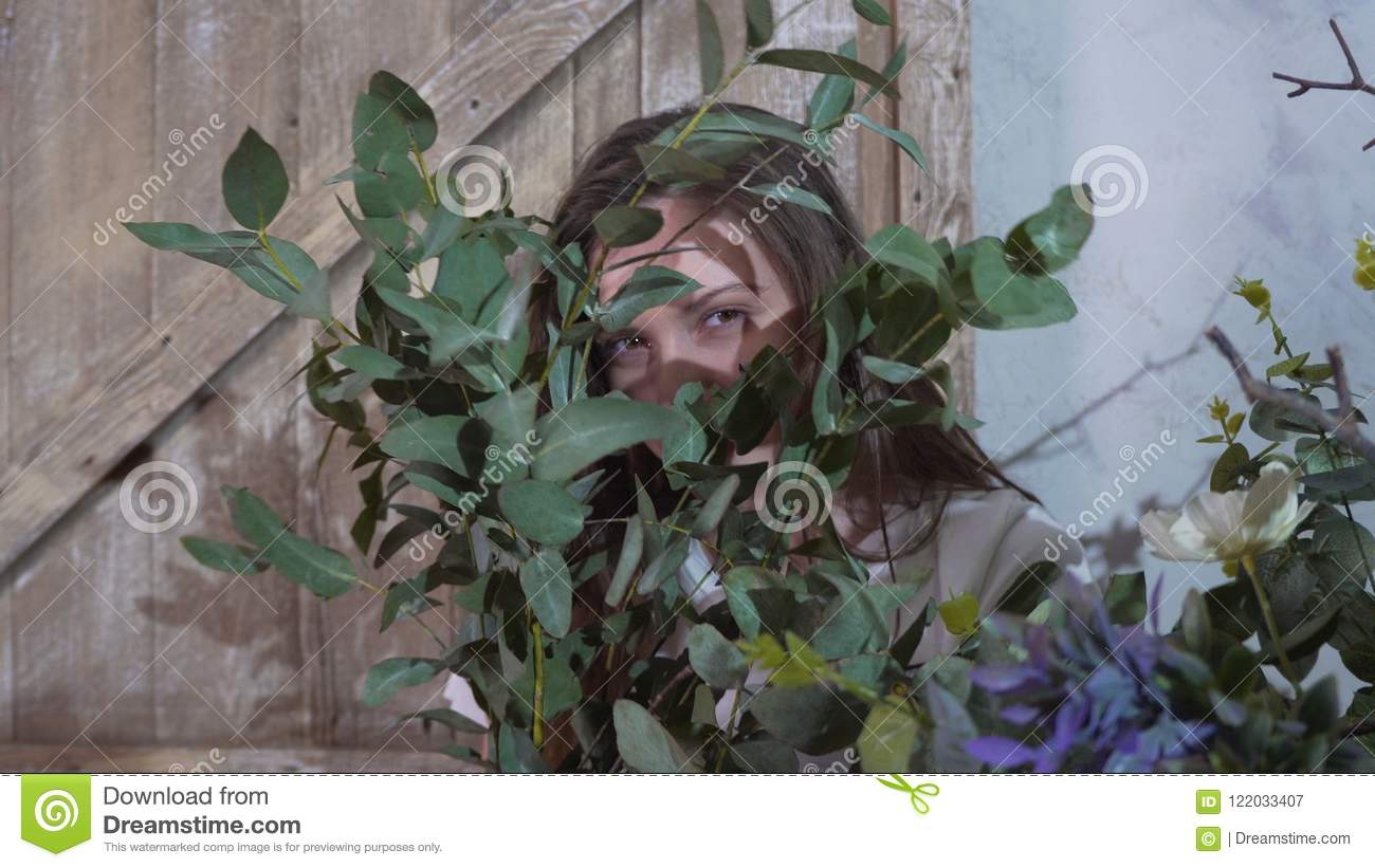 The girl hides her eyes behind the bunch of eucalyptus
