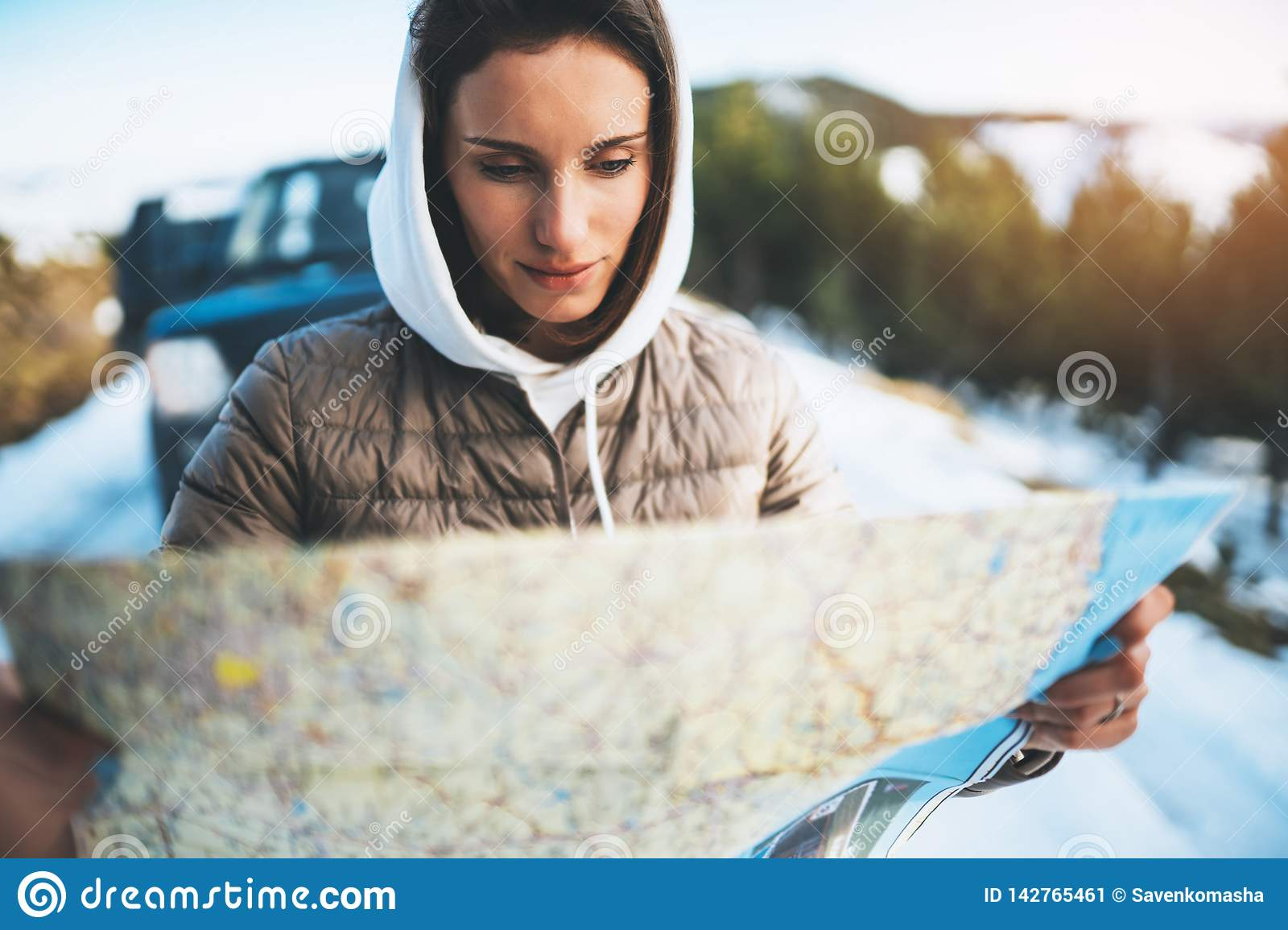 Girl hold in hands looking on map, people planning trip in snow mountain, relax tourist travels by auto car, hipster enjoy winter