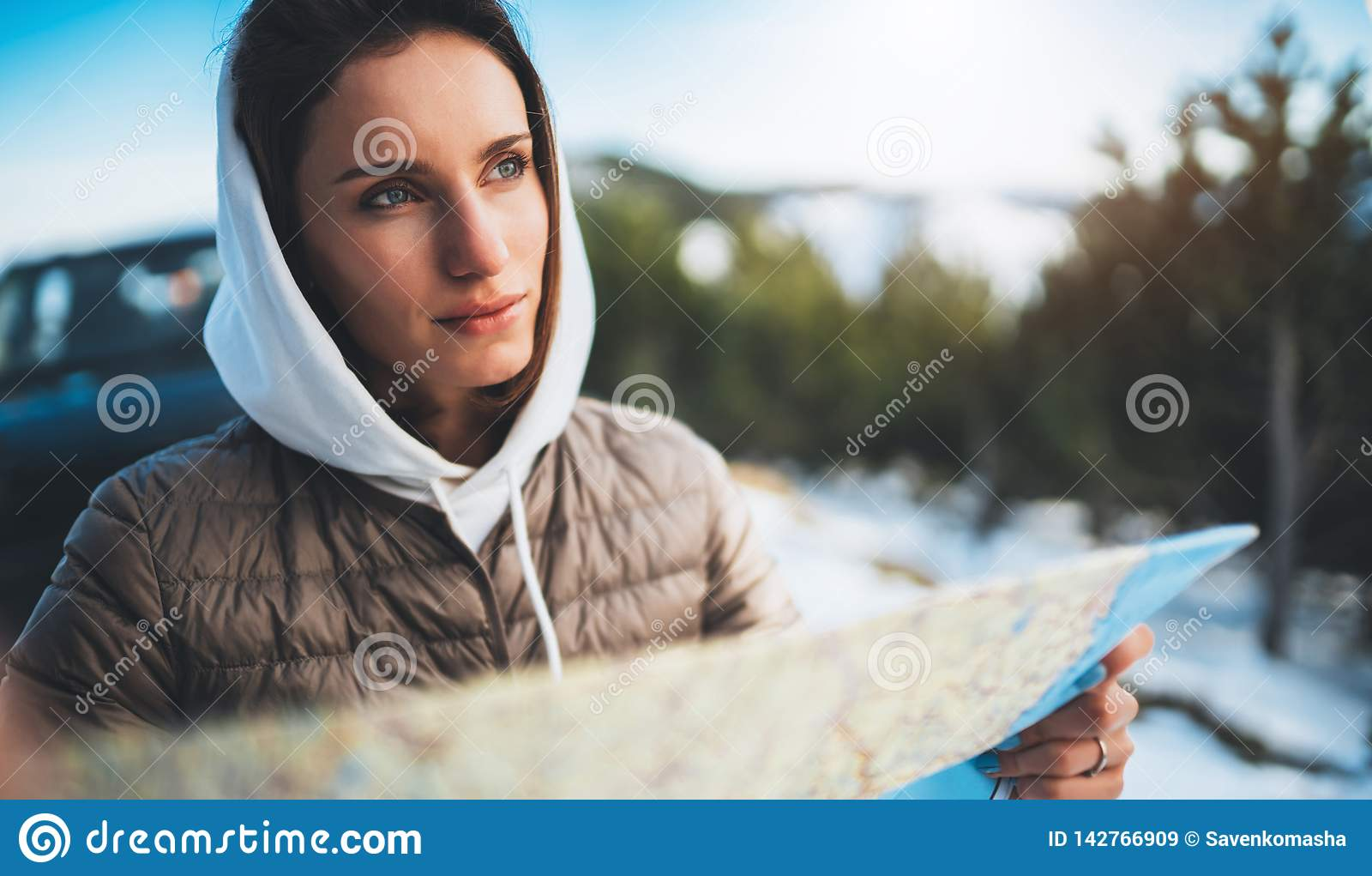 Girl hold in hands looking on map, relax tourist travels by auto car, people planning trip in snow mountain, hipster enjoy winter