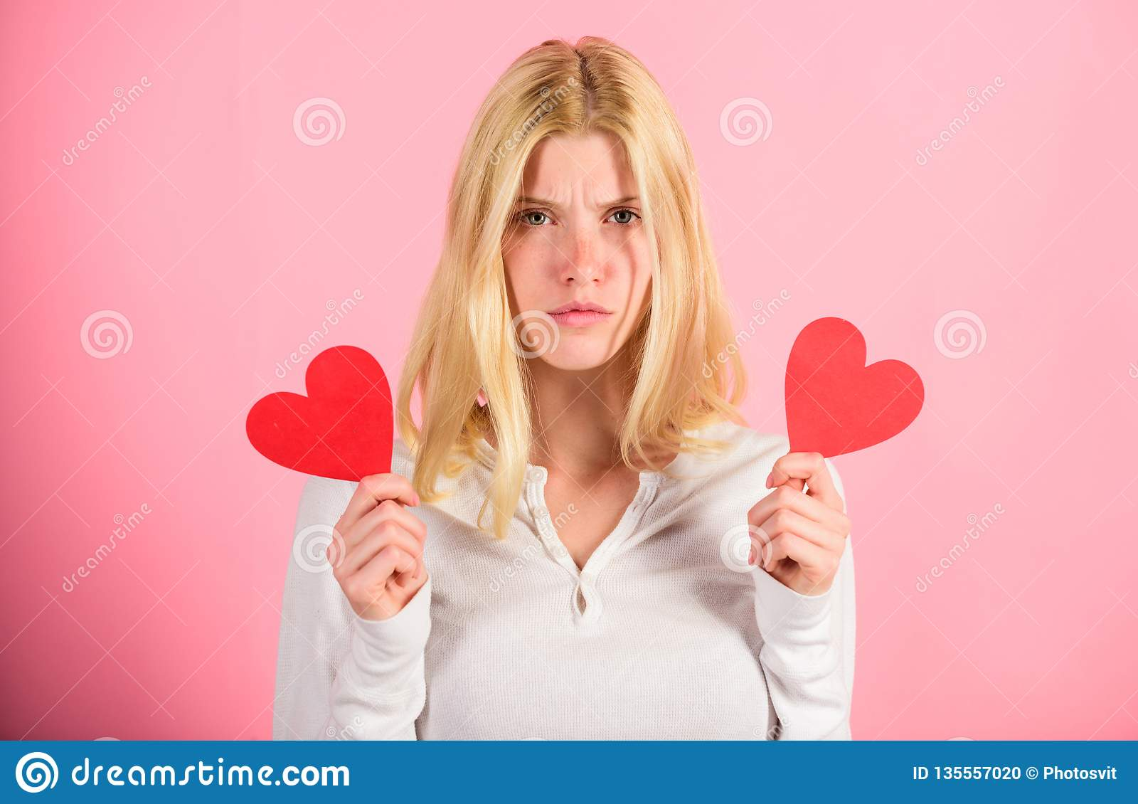 Girl hold heart love symbol over pink background. Valentines day concept. How to feel less lonely on valentines day
