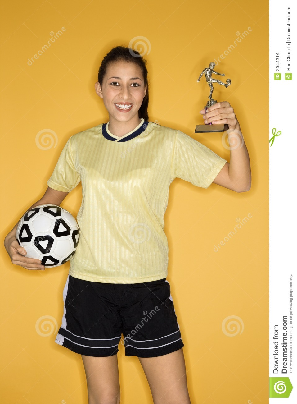 Girl holding ball and trophy.