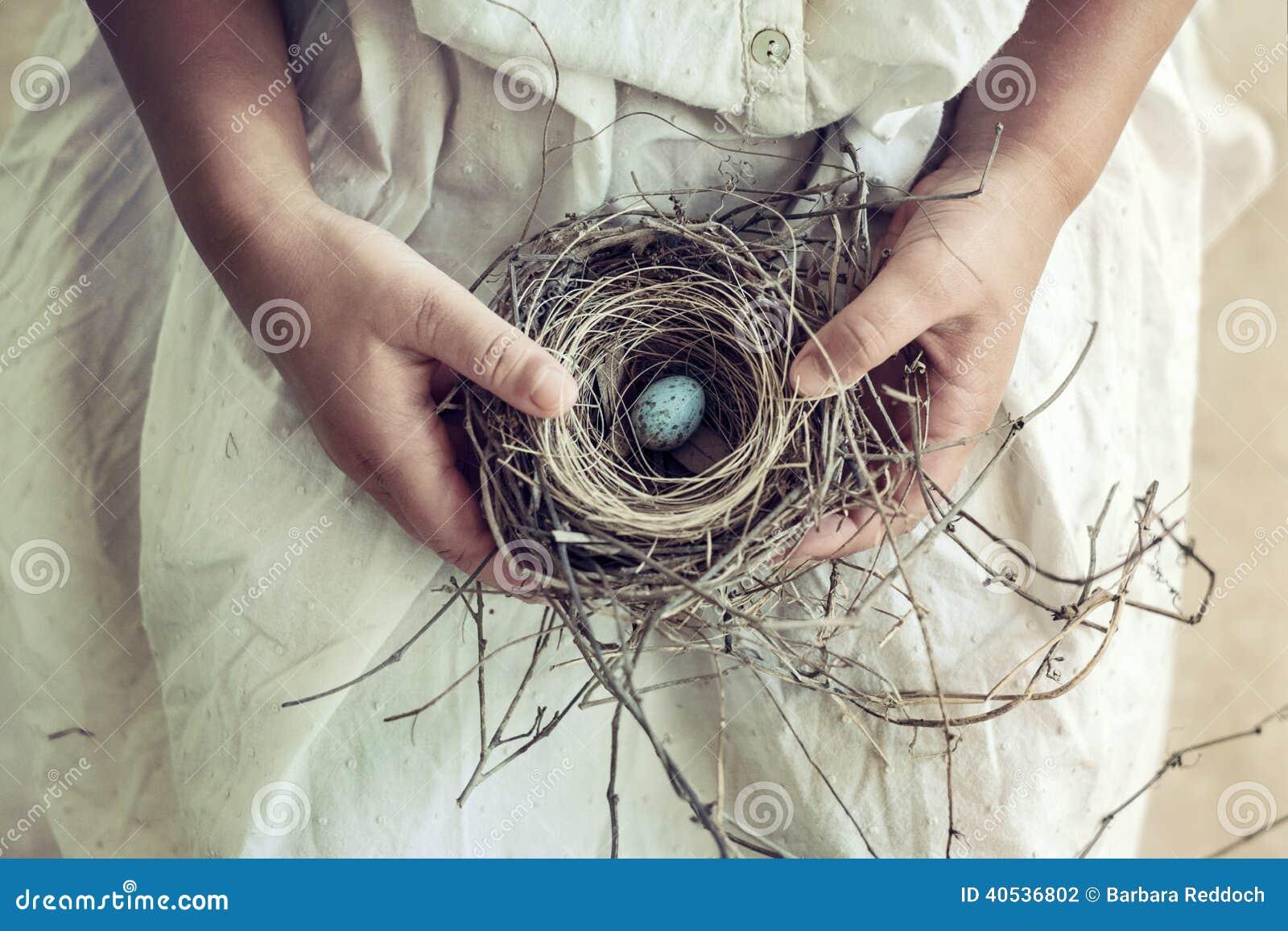 Girl Holding Blue Speckled Egg in Bird Nest on Lap