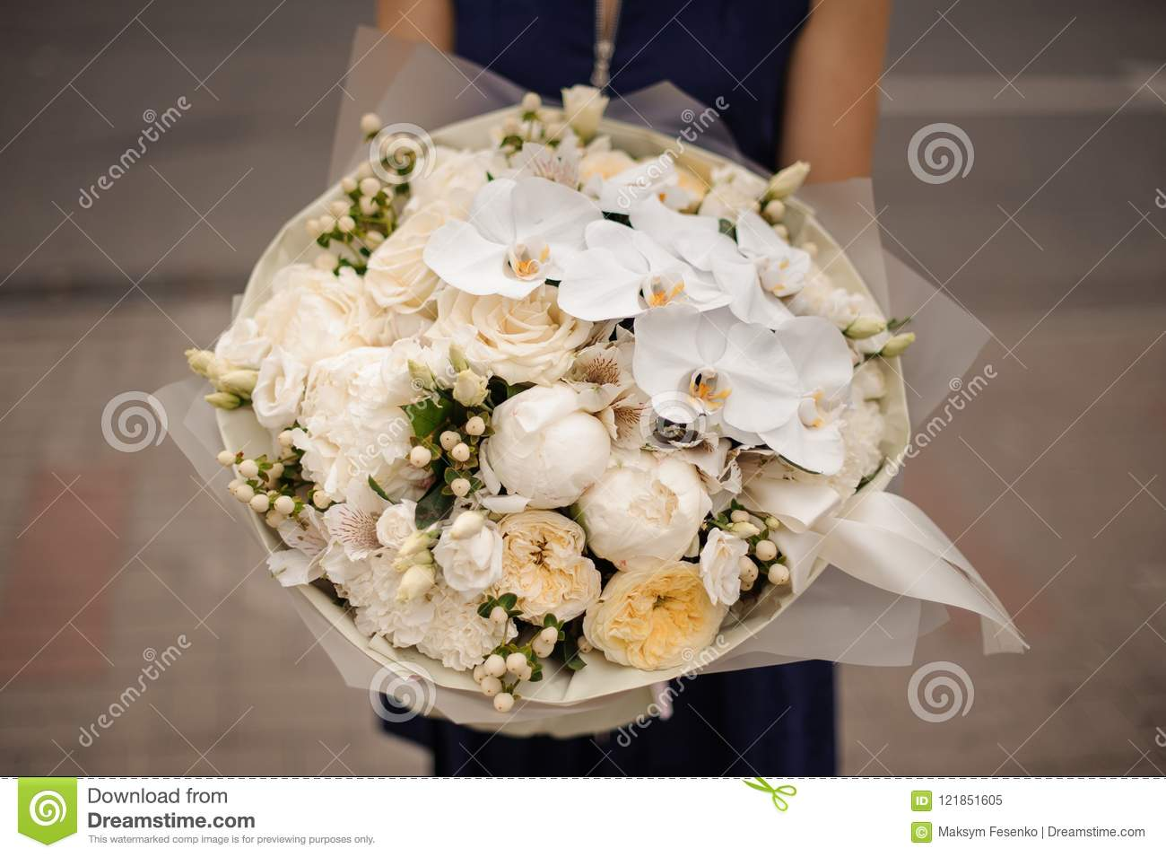Girl holding bouquet of white orchids and champagne color peonies and roses