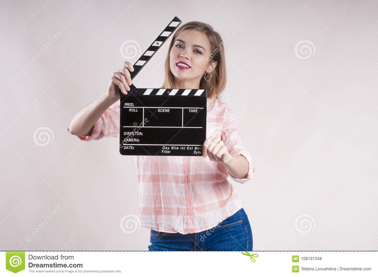 Girl is holding a clapperboard and posing. producer start on white background