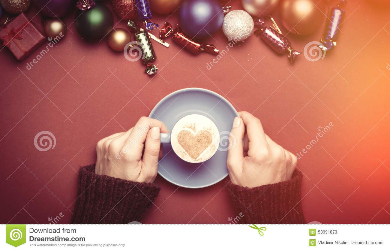 Girl holding cup of coffee near christmas toys.