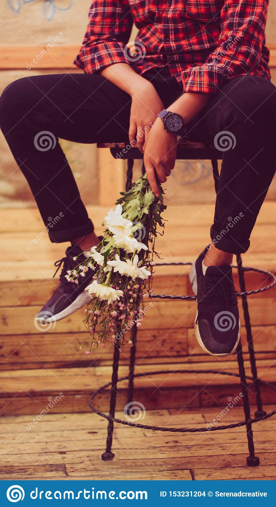 A girl holding a flower boquet on the chair in a coffee shop