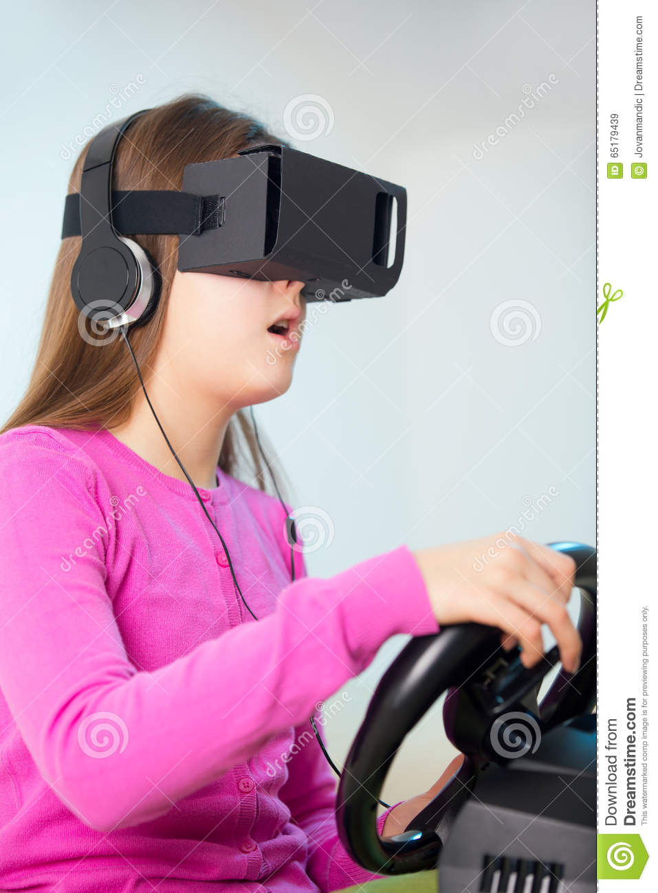 38bc502a166 Girl holding a gaming computer wheel getting experience using VR-headset  glasses