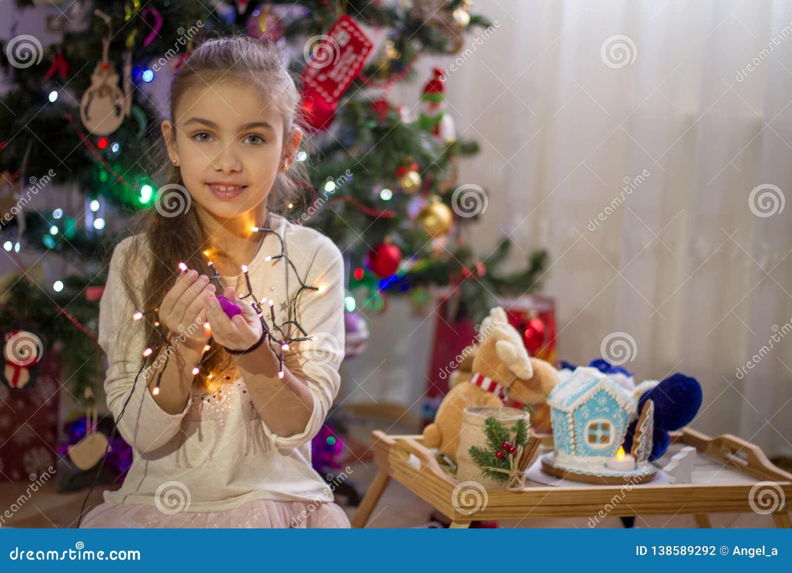 Girl holding lights over Christmas decoration