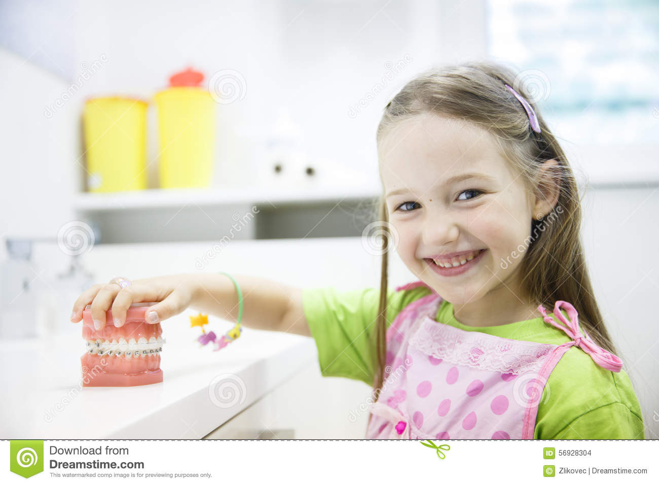 Girl holding model of human jaw with dental braces