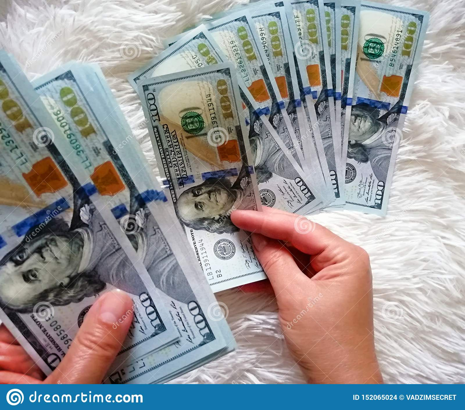 The girl is holding the money in her hands. One hundred dollars cash