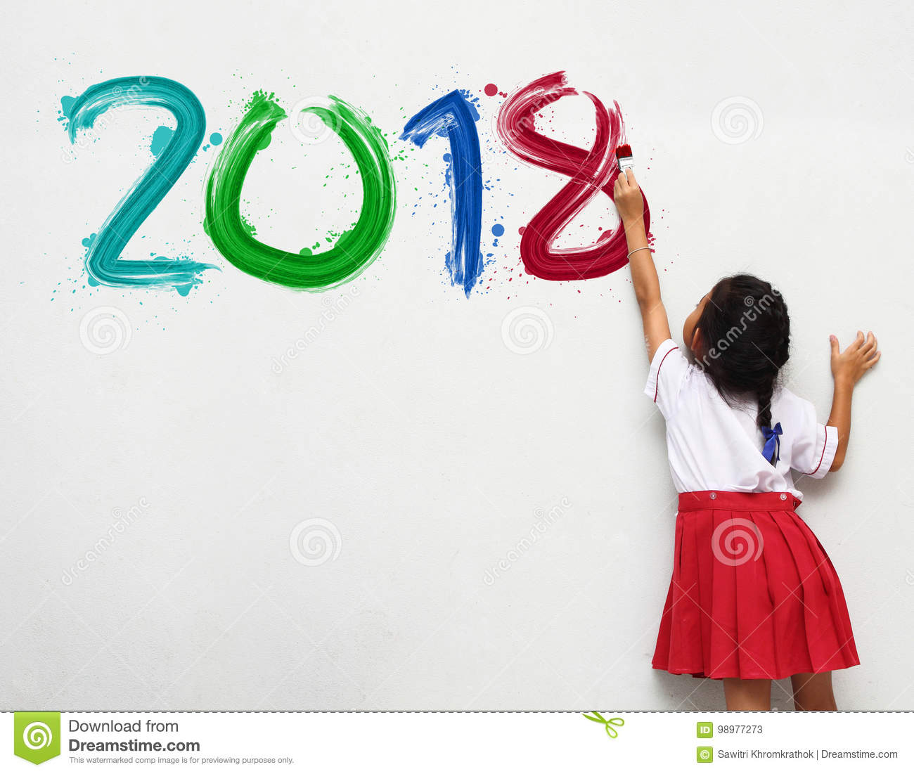 Girl holding a paint brush painting happy new year 2018