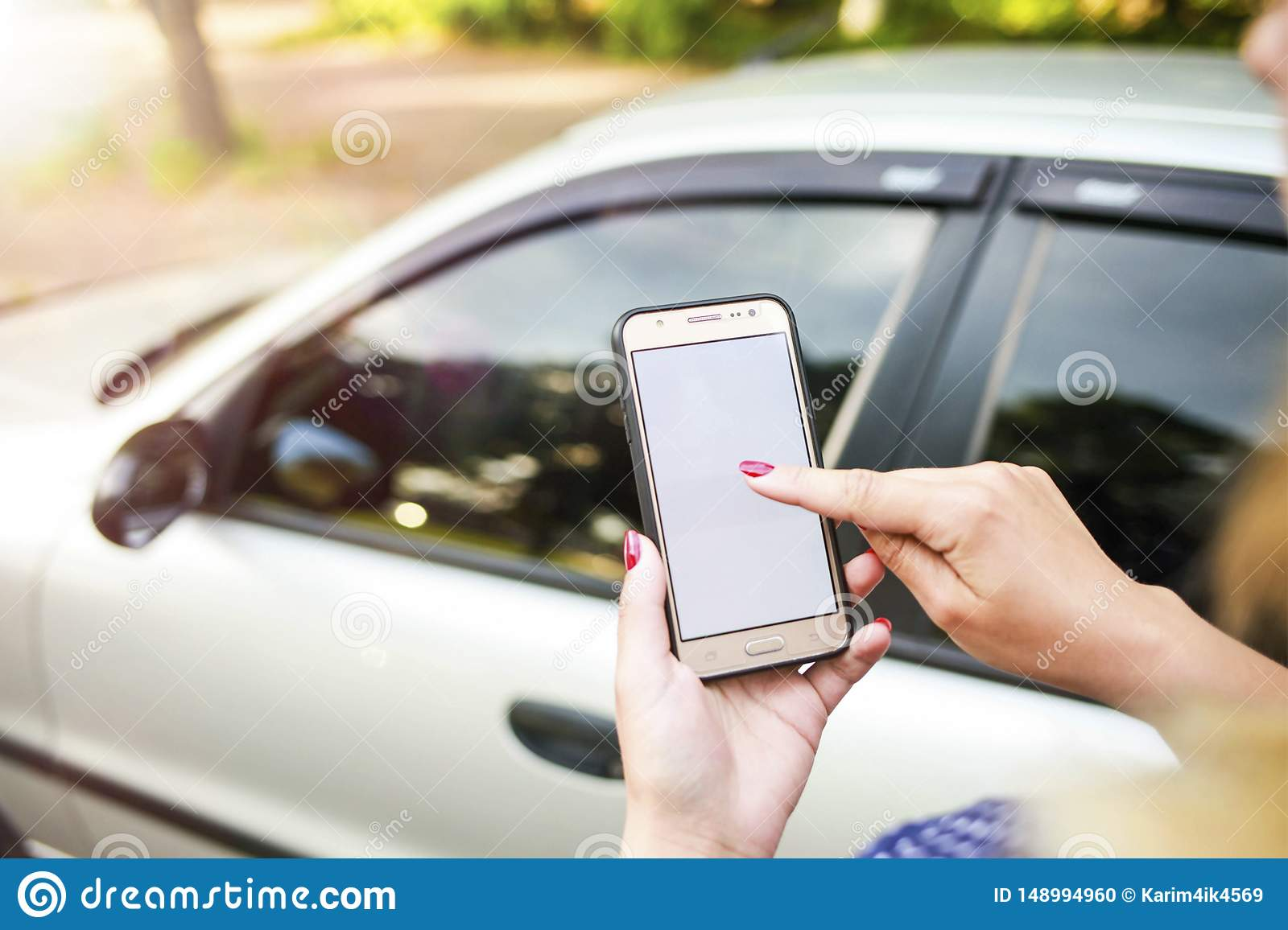 Girl holding a phone in the background of the car. Theme car rental using phone car sharing