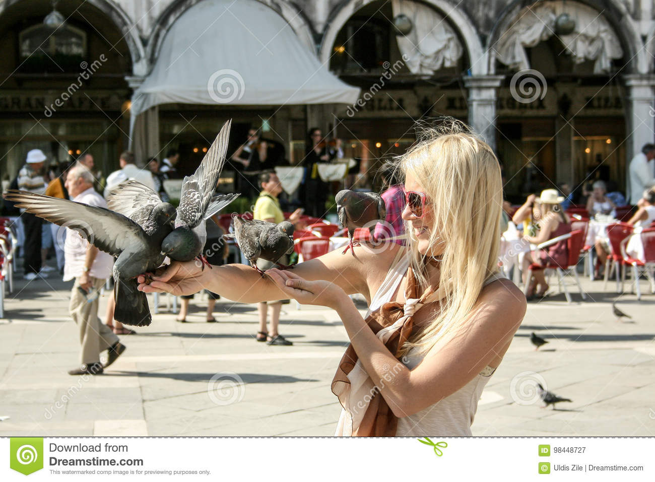 Girl holding pigeons in Piazza San Marco Venice Italy.
