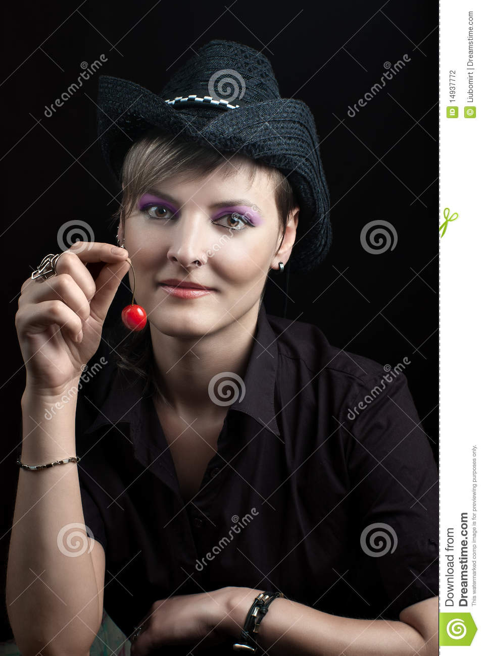 ba2d3b1bbb5 Young woman in black hat holding red cherry against dark background