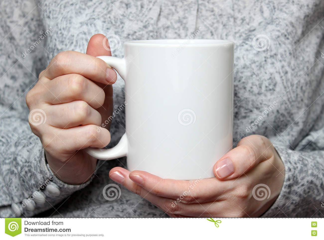Girl is holding white cup in hands. White mug in woman s hands.