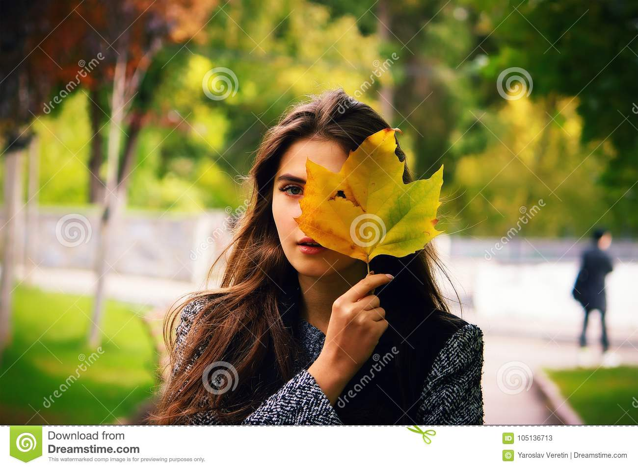 Girl holding yellow leaf, looking through hole autumn background
