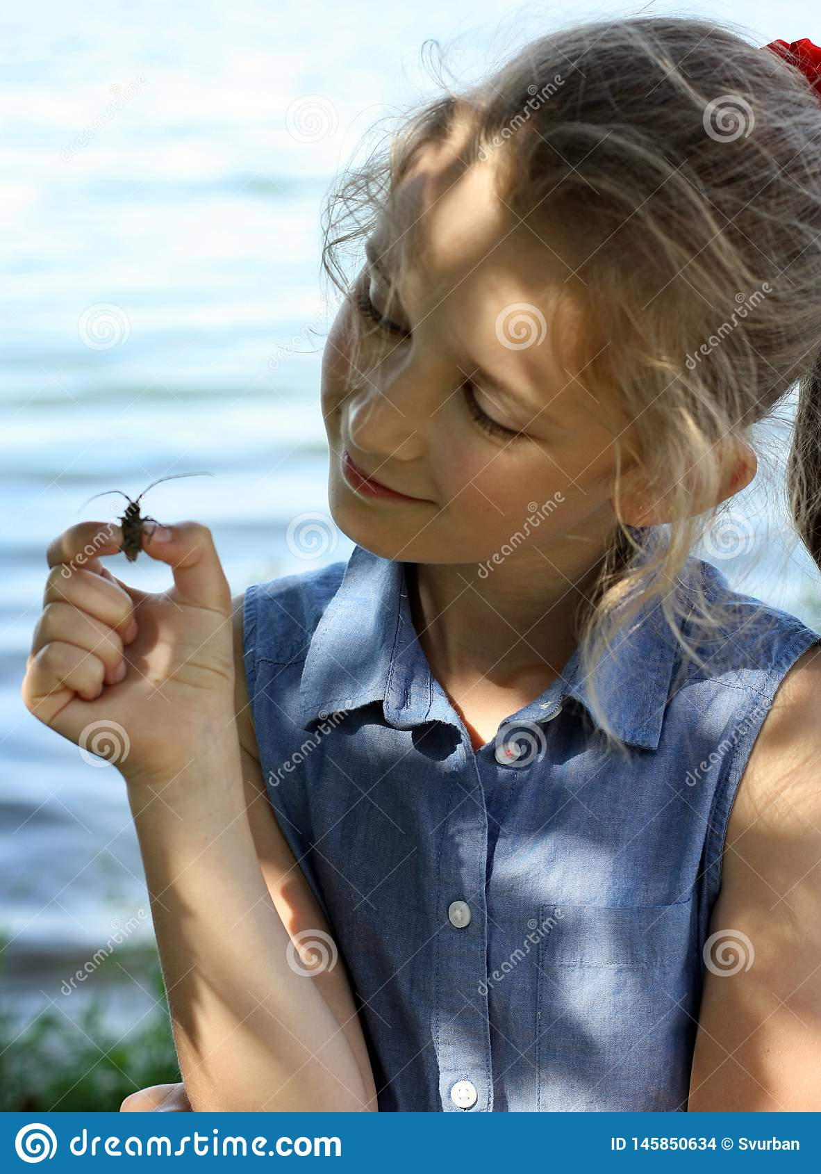 The girl holds a beetle on a hand